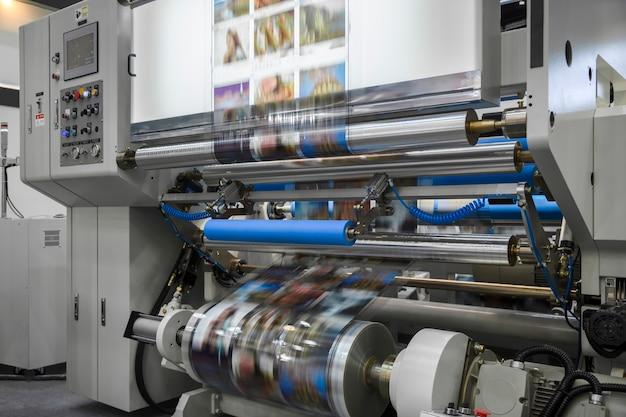 Grote offsetdrukpers of tijdschrift met een lange papierrol in de productielijn van een industriële printermachine.