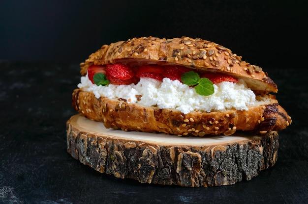 Grote ontbijtgranencroissant met kwark en verse aardbeien op een donkere achtergrond