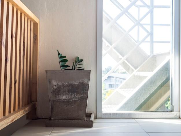 Grote oude geometrische betonnen pot met groene bladerendecoratie bij de glazen deur naar buiten bij de nooduitgang in het gebouw.