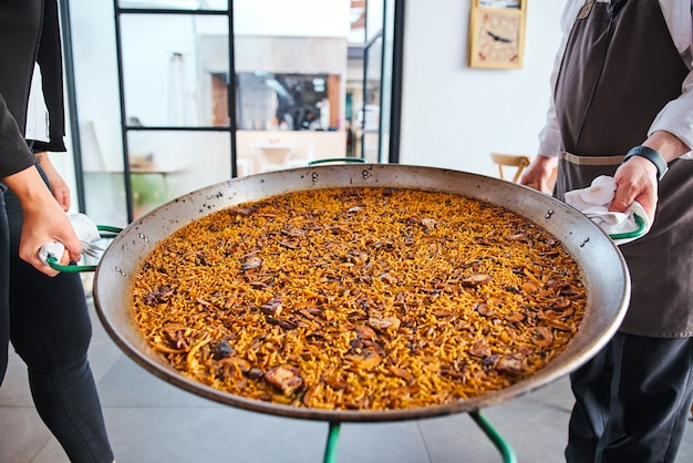 Grote paella haal de afgewerkte maaltijd eruit