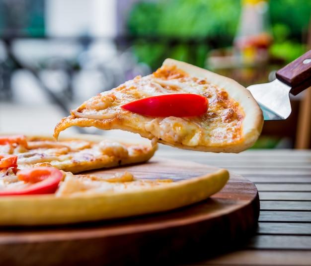 Grote pizza op een houten tafel.