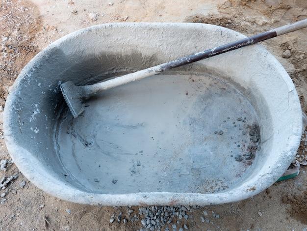 Grote plastic emmer voor het mengen van de cementmortel.