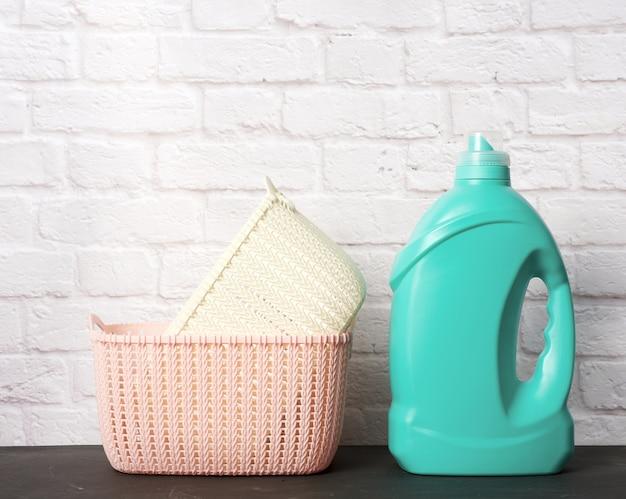 Grote plastic fles met vloeibaar wasmiddel en een stapel manden tegen een witte bakstenen muur