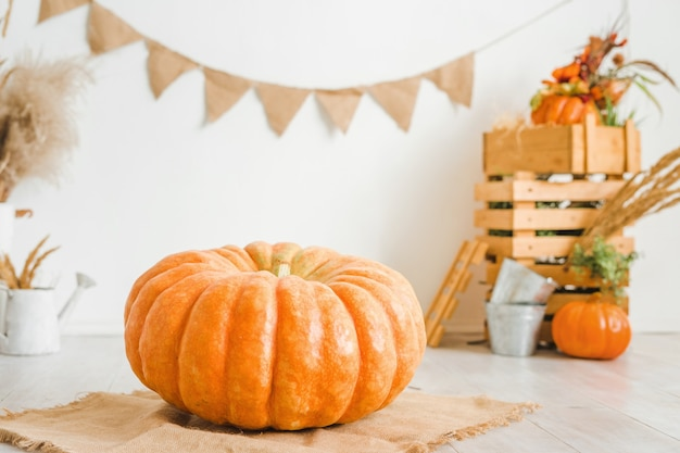 Grote pompoen op een witte achtergrond herfst decor met houten kisten en droge aartjes