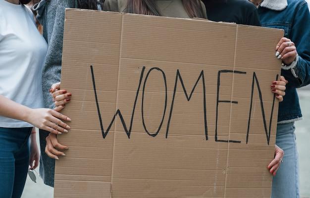 Grote poster houden. een groep feministische vrouwen protesteert buitenshuis voor hun rechten