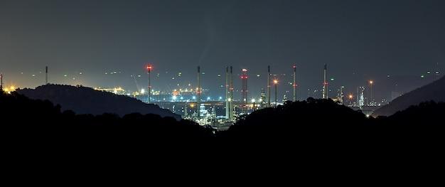 Grote raffinaderij achter de berg in de nacht