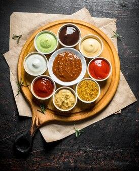 Grote reeks sauzen op snijplank met papier op donkere rustieke tafel