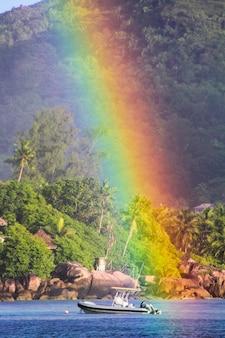Grote regenboog over tropisch eiland en luxe hotel