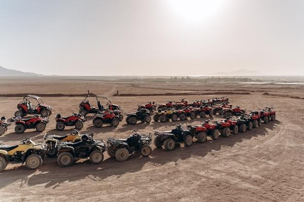 Grote rij atv's en buggy's staan midden in een zandwoestijn
