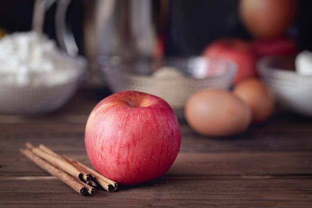Grote rode appel met pijpjes kaneel en basisingrediënten voor het koken van appeltaart op donkere bruine achtergrond