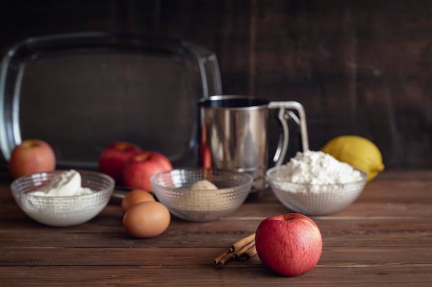 Grote rode appel met pijpjes kaneel en basisingrediënten voor het koken van appeltaart op donkere houten bruine achtergrond