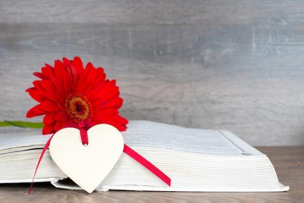 Grote rode bloem met geopende boek en hart vorm op rustieke houten tafel