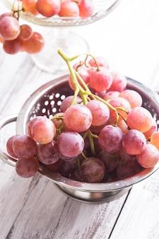 Grote rode druiven in vergiet op de houten achtergrond