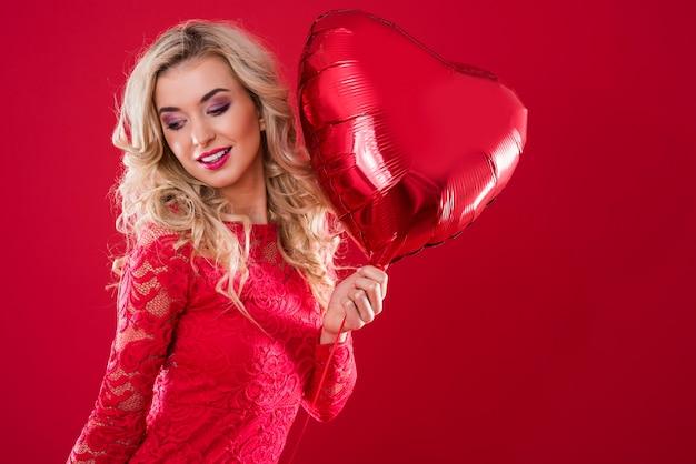 Grote rode hartvormige ballon die door een vrolijke vrouw wordt vastgehouden