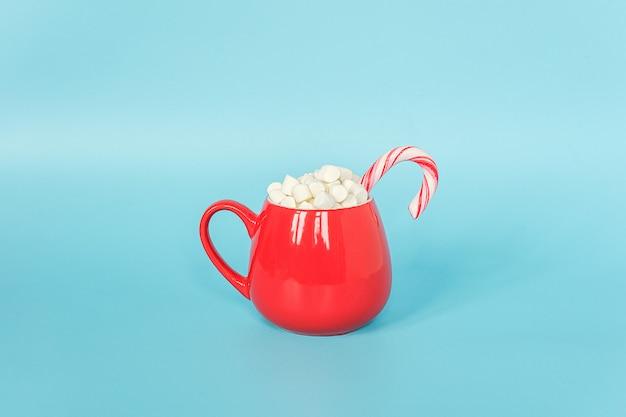 Grote rode kop marshmallows met lollyriet op blauw