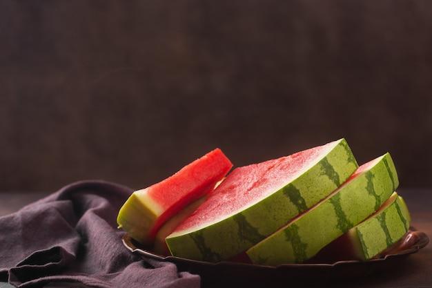Grote rode rauwe watermeloenstukken op donkere achtergrond