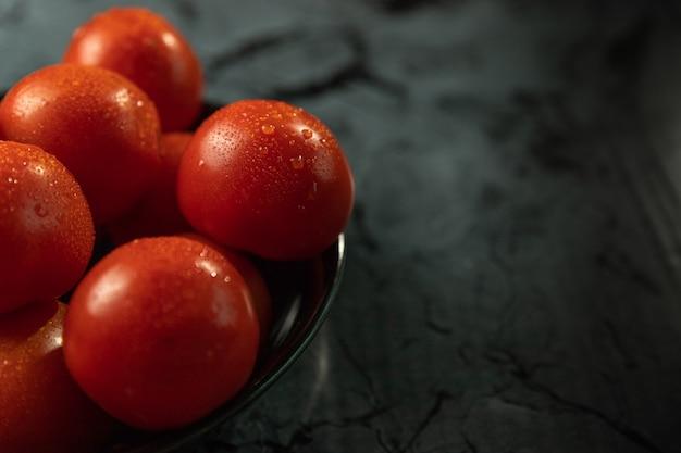 Grote rode tomaten op een zwarte plaat, op een granieten tafel