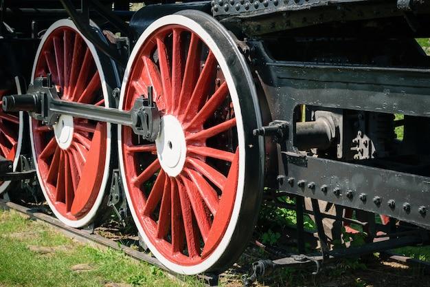 Grote rode wielen van de oude klassieke treinen op de rails.