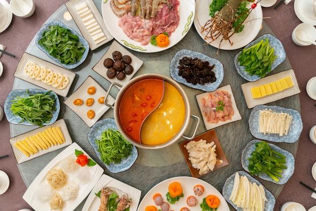 Grote ronde tafel met daarop verschillende bijgerechten met in het midden soep