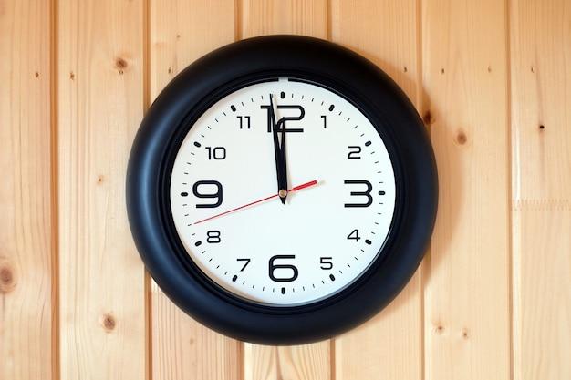 Grote ronde wandklok met een zwarte rand met pijlen weergegeven: twaalf uur hangt aan bruine houten muur van verticale planken horizontale weergave binnen close-up