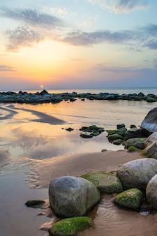 Grote rotsblokken op de voorgrond en een strook kleine rotsen. rotsachtig strand van de golf