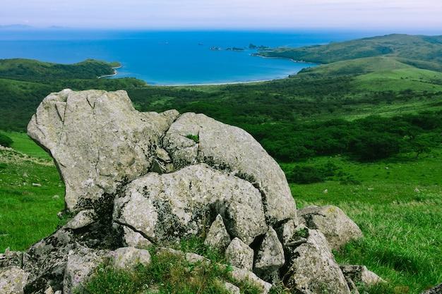 Grote rotsen bovenop de heuvel, zomerzee.