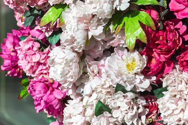 Grote roze en rode kunstmatige pioenrozen aan de muur. gevoelige bloementextuur als achtergrond voor huwelijksscène, feestelijk decor.