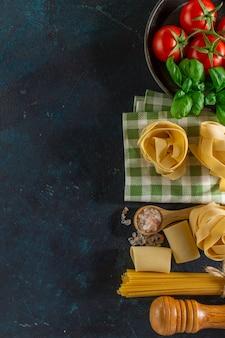 Grote samenstelling met verscheidenheid van pasta, tomaten en basilicum