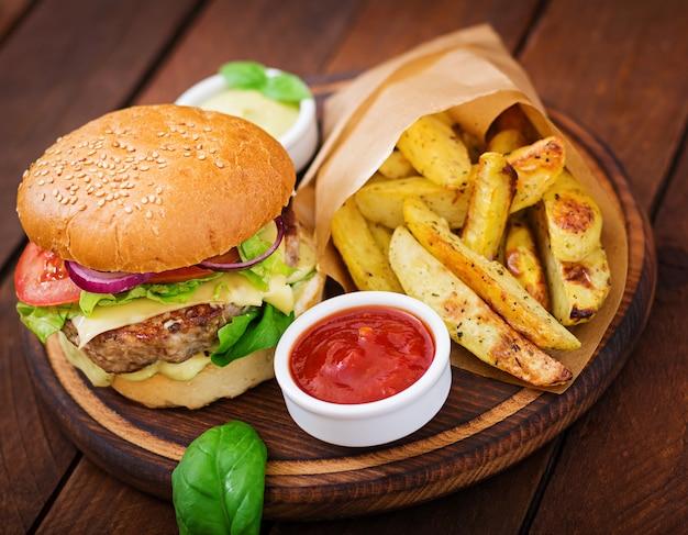 Grote sandwich - hamburger met sappige rundvlees hamburger, kaas, tomaat en rode ui op houten tafel