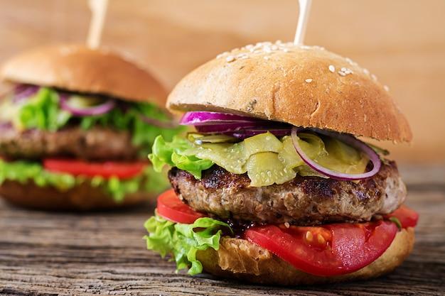 Grote sandwich - hamburgerburger met rundvlees, tomaat, kaas en ingelegde komkommer.