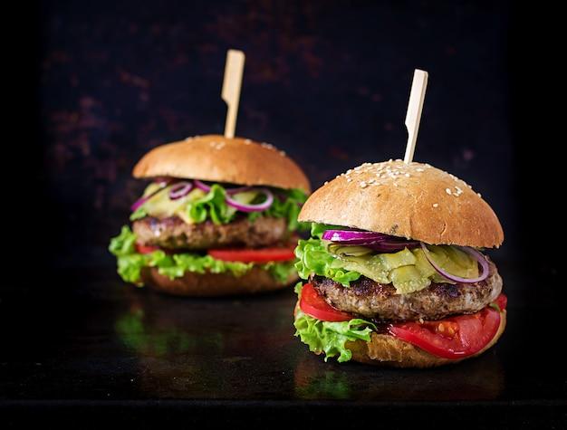 Grote sandwich - hamburgerhamburger met rundvlees, tomaat, kaas en ingelegde komkommer.