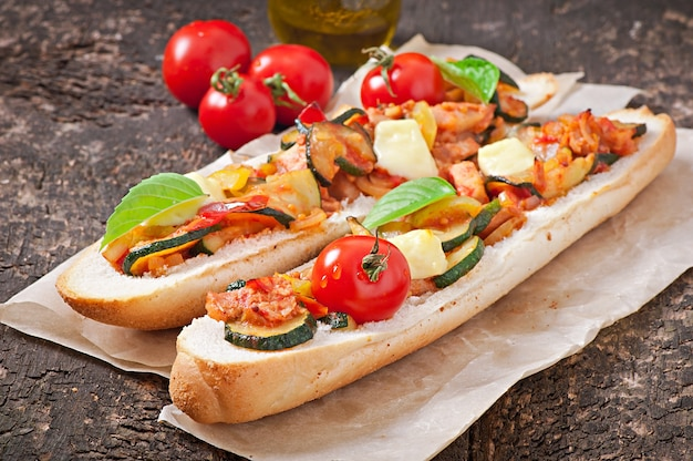 Grote sandwich met geroosterde groenten met kaas en basilicum op oude houten oppervlak