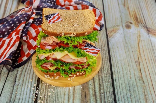 Grote sandwich met ham, kaas en tomaat voor amerikaanse vakantie tafel.