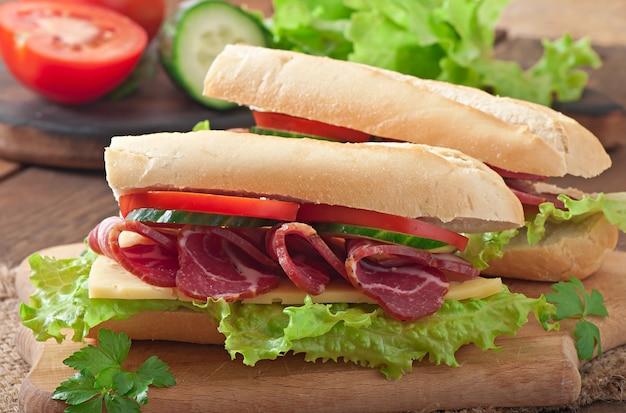 Grote sandwich met rauw gerookt vlees op een houten achtergrond