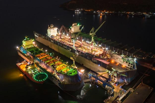 Grote scheepswerf en scheepsreparatie op de zee bij nacht