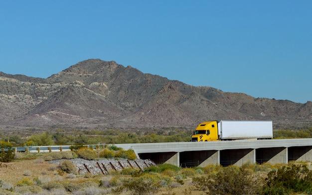 Grote semi-vrachtwagen voor lange afstanden met twee vlakke opleggers die over de kronkelende weg met brug rond de bergrots vervoeren