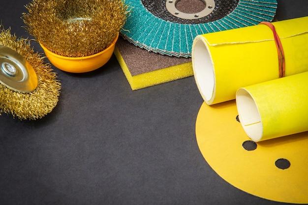 Grote set van schuurmiddelen en geel schuurpapier op zwart