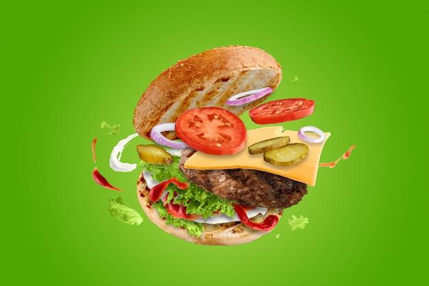Grote smakelijke hamburger met vliegende elementen