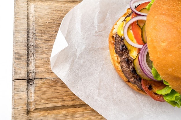 Grote smakelijke zelfgemaakte hamburger op een houten bord. bovenaanzicht plat lag met kopie ruimte voor uw tekst