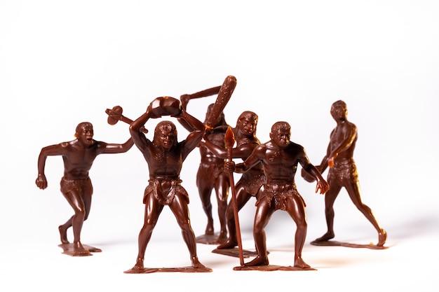 Grote speelgoedfiguren van primitieve mensen op een witte achtergrond.