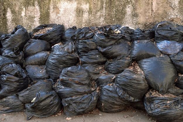 Grote stapel afval of bladeren in zwarte plastic zakken ligt buiten op een asfaltoppervlak. het concept van vervuilingsomgeving.