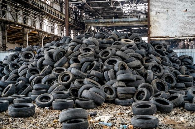 Grote stapel autobanden op de kapotte fabriek.