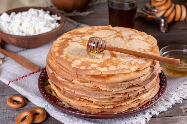 Grote stapel dunne pannenkoeken met honing. russische bliny. maslenitsa. rustieke stijl, close-up bekijken