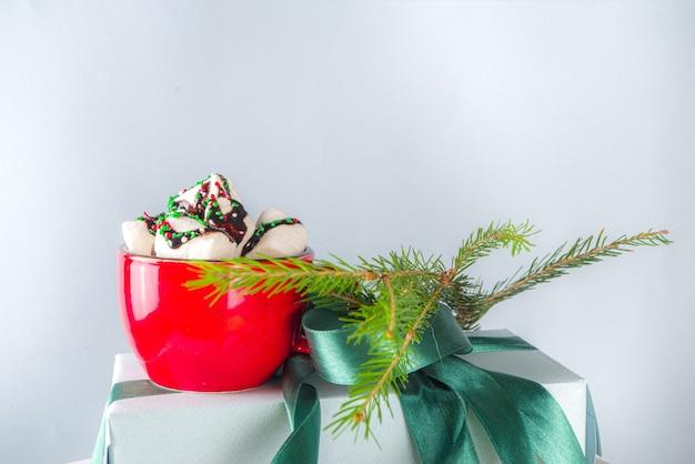 Grote stapel kerstcadeaus met warme chocolademelk, blijf erop als voetstuk, gezellige pastelkleurige geschenkdozen van ambachtelijk papier met groen feestelijk kerstlint, kopje cacao met marshmallow, kopieer ruimte