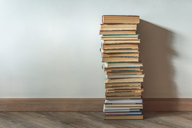Grote stapel oude boeken over witte muur