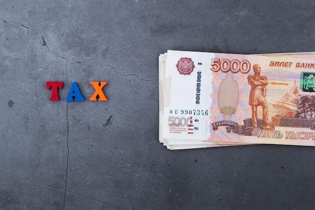 Grote stapel russische geldbankbiljetten van vijfduizend roebel die op een grijze cementoppervlakte liggen.
