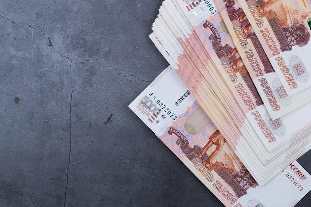 Grote stapel russische geldbankbiljetten van vijfduizend roebels die op een grijs cement liggen.