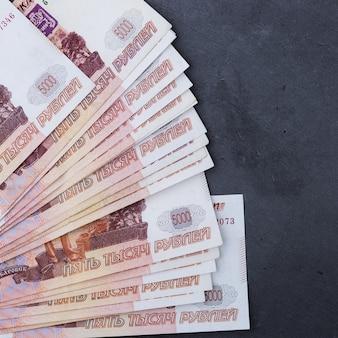 Grote stapel russische geldbankbiljetten van vijfduizend roebels die op een grijze achtergrond liggen