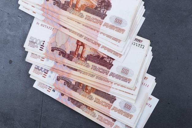Grote stapel russische geldbankbiljetten van vijfduizend roebels die op een grijze cementachtergrond liggen.