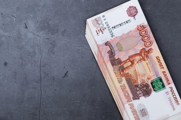 Grote stapel russische geldbankbiljetten van vijfduizend roebels die op grijs cement liggen.